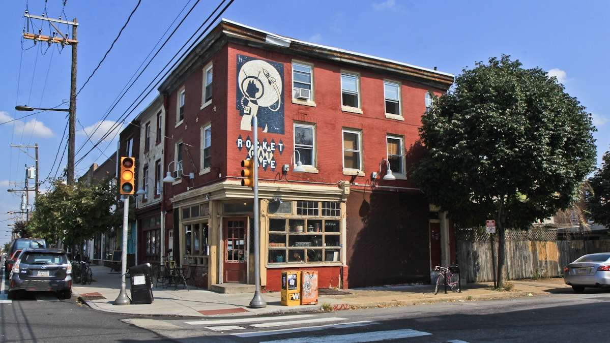 The Shepard Fairey wheatpaste on the Norris Street side of Rocket Cat Cafe went up in 2010 and is now covered with a brown tarp until owner Karen Breese decides how to revive the mural. (Kimberly Paynter/WHYY)