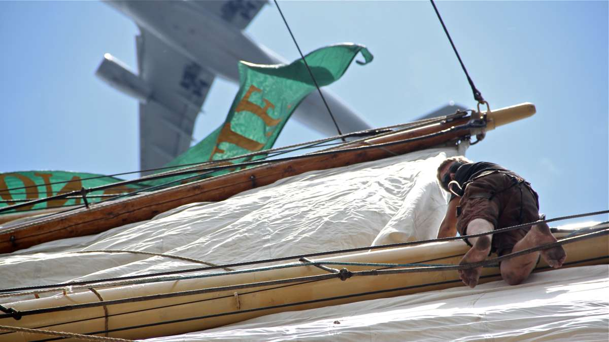 Emil Visby climbs high into the rigging to free a sail. (Emma Lee/WHYY)