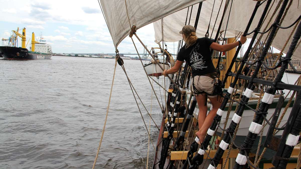Erin Greig hangs from the rigging of the Picton Castle as she frees some lines. (Emma Lee/WHYY)