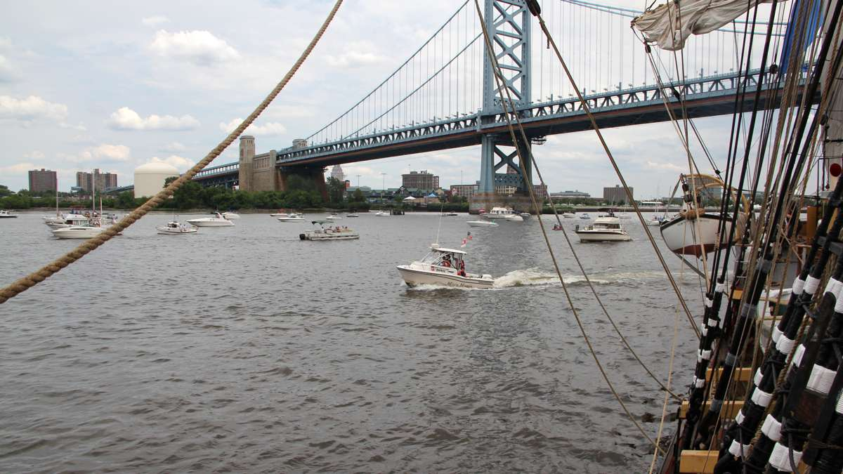 Small pleasure boats gather under the Ben Franklin Bridge to watch the arrival of the tall ships. (Emma Lee/WHYY)