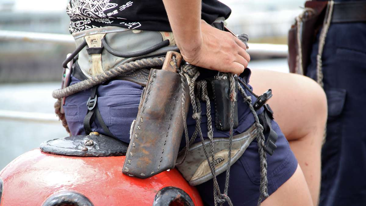The ship's crew wear their tools everywhere, including fixed-blade knife, marlin spike and harness for security in the rigging. (Emma Lee/WHYY)