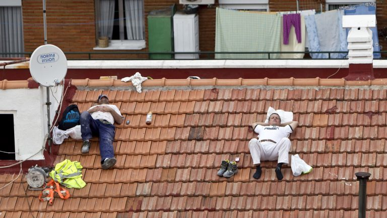 Two workers take a nap on a roof in Madrid, Spain. (AP Photo/Alberto Di Lolli, File)