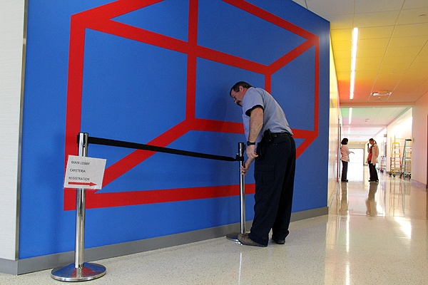 <p>A custodian arranges a temporary cordon around a work by Sol LeWitt at Einstein Medical Center. Montgomery, to keep it pristine until the unveiling on Wednesday. (Emma Lee/for NewsWorks)</p>