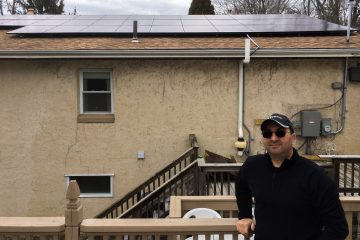 Sal Fede displays his new solar panels mounted on the roof of his Philadelphia home. (Joel Wolfram/for WHYY)