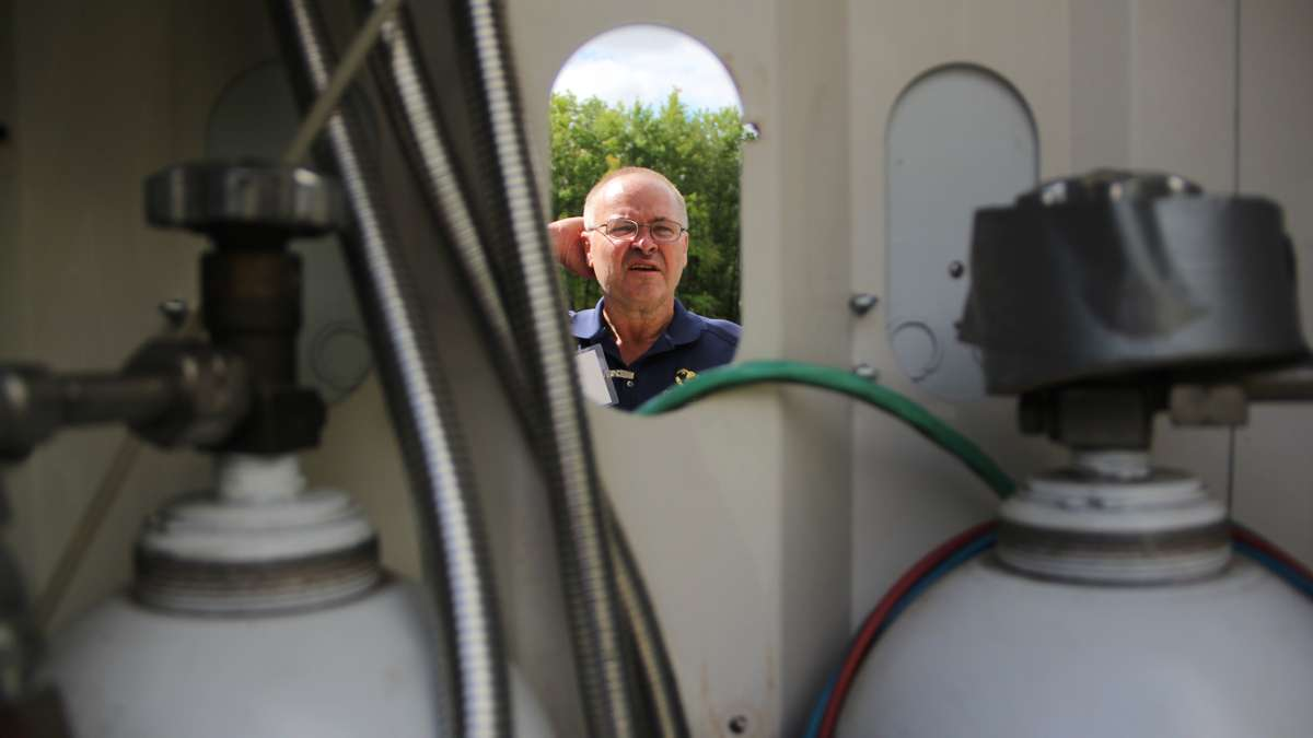 Mike Stanski examines a portable power station that stores the product of solar and wind power in hydrogen tanks. The Joule Box is marketed as an alternative to gas powered generators. (Emma Lee/WHYY)