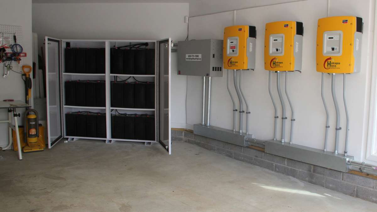 In the garage, batteries (left) store energy while a series of panels regulate the flow between the solar panels, the hydrogen tank and the house. The system also sells energy back to the grid once its own needs are met. (Emma Lee/WHYY)