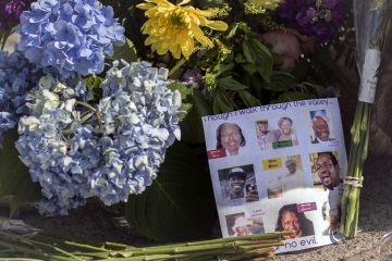 Flowers and notes of hope and support from the community line the sidewalk, Friday, June 19, 2015  in front of the  Emanuel AME Church in Charleston, S.C. Dylann Storm Roof, 21, is accused of killing nine people during a Wednesday night Bible study at the church.  (AP Photo/Stephen B. Morton)