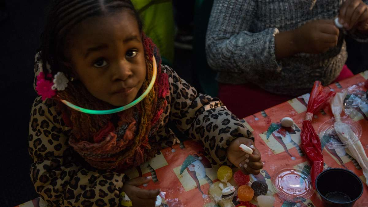 Two year old Malaya Mulligan works on her cookie creation inside the Ben's Sweets and Treats tent.