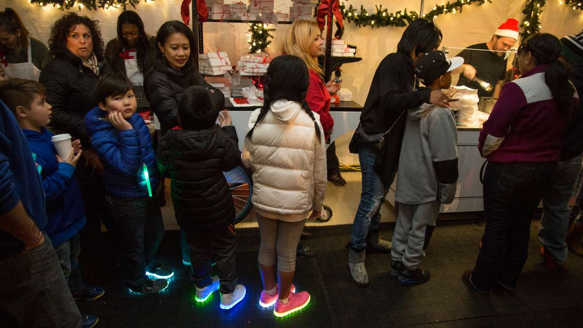 Familes wait in line for fresh donuts at The Franklin Square Holiday and Light Festival. The festival runs November 10 through December 31 and is free to the public.