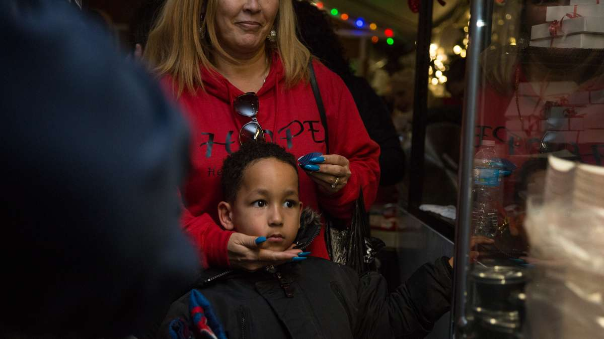 Visitors watch intently as a man makes and fries donuts at The Franklin Square Holiday and Light Festival. The festival runs November 10 through December 31 and is free to the public.