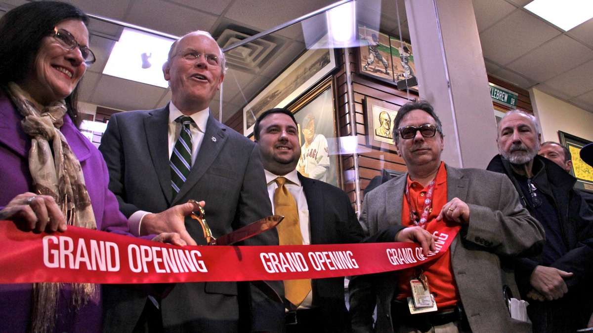 Former Collingswood Mayor Jim Maley cuts the ribbon held by members of the DePace family. (Emma Lee/WHYY)