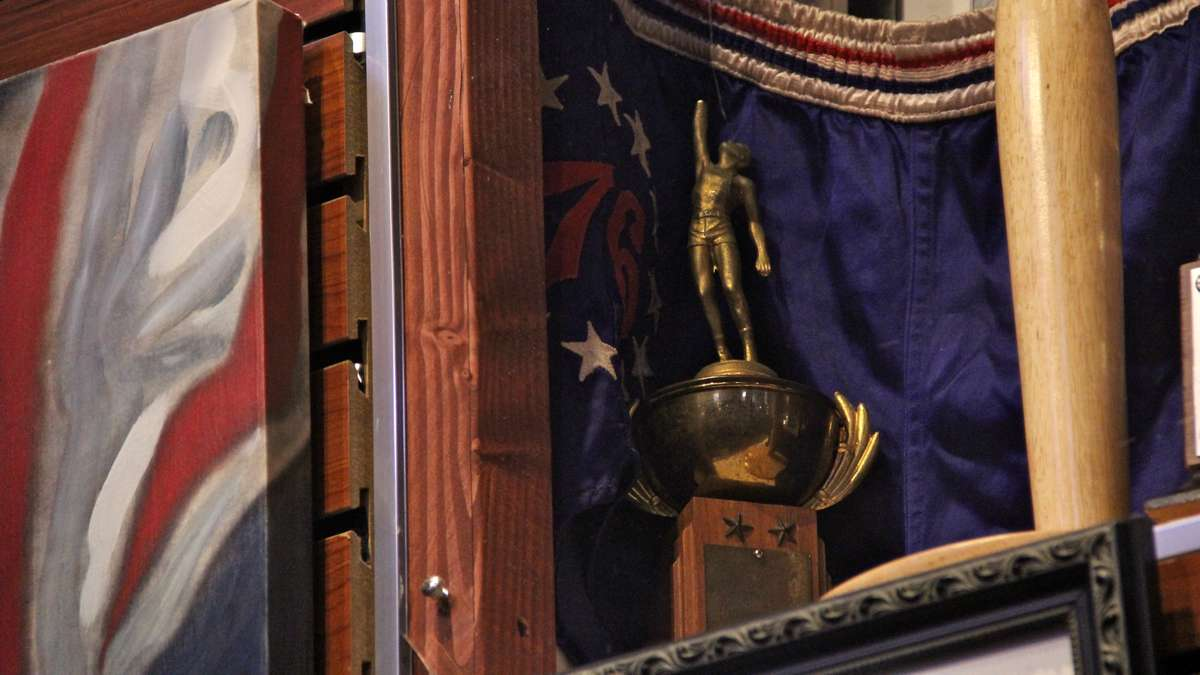 Tucked away in the corner of a shadowbox is a small trophy commemorating Wilt Chamberlain's 75-point performance when he played for Overbrook High School. (Emma Lee/WHYY)