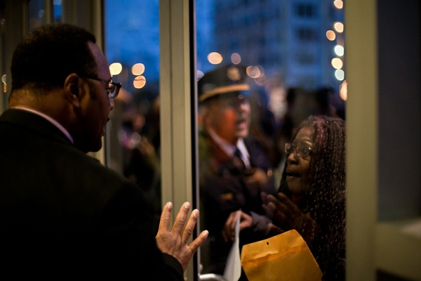 <p><p>A woman concerned that she would not get a seat at the School Reform Commission meeting Thursdaytalks through the front door to a Philadelphia police officer. (Brad Larrison/for NewsWorks)</p></p>
