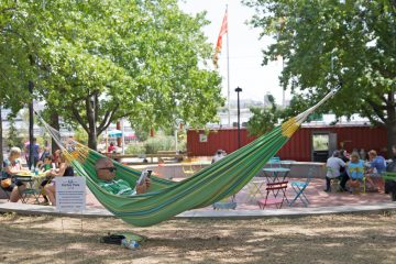 Brett Mapp reads a book in one of the hammocks at Spruce Street Harbor Park on the waterfront in Philadelphia, Pa.  (Lindsay Lazarski/WHYY)