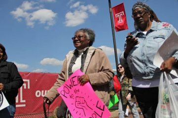 Jacqueline Wiggins (center), a long time resident of the Temple University area, joins her neighbors and students in an April 2016 protest march against a proposed new football stadium. (Emma Lee/WHYY)