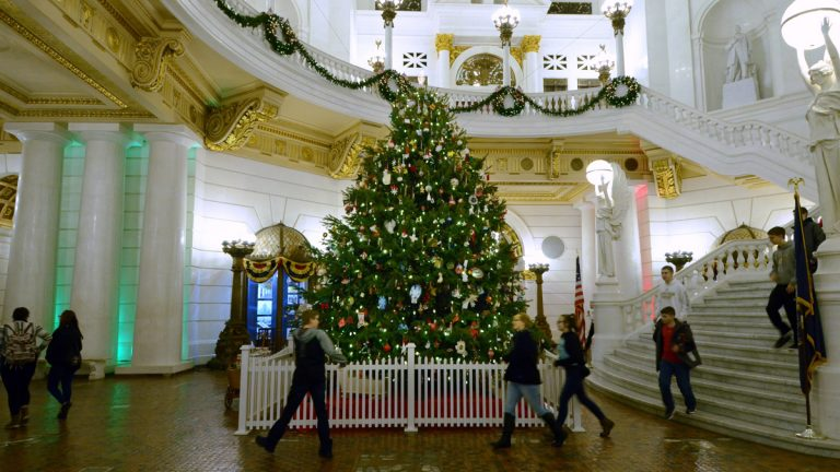A school group walks by the 22-foot-tall Douglas Fir that stands in the Pennsylvania Capitol Rotunda as part of the annual Christmas decorations around the building. (AP Photo/Marc Levy)