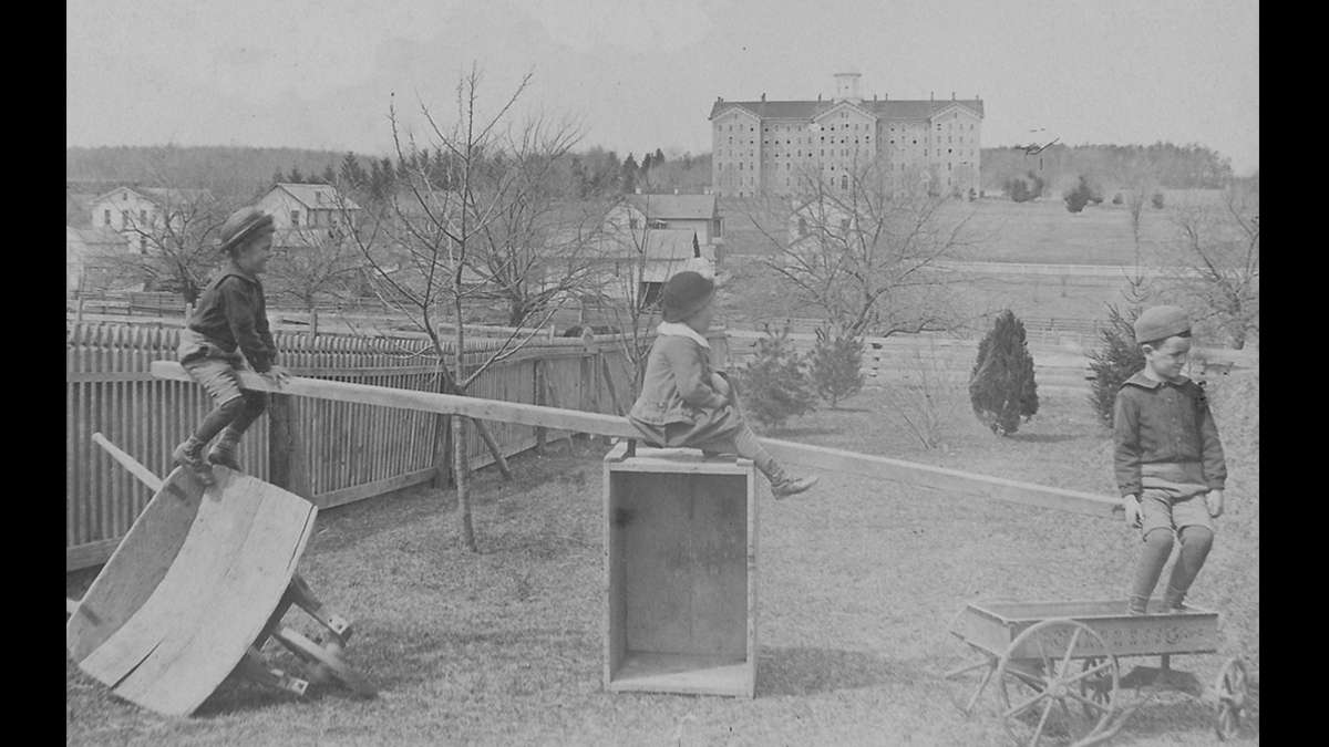 Children play near Pugh Street and Beaver Avenue in State College, Pennsylvania with the original Old Main in the distance circa 1885. (Image courtesy of the Centre County Historical Society)