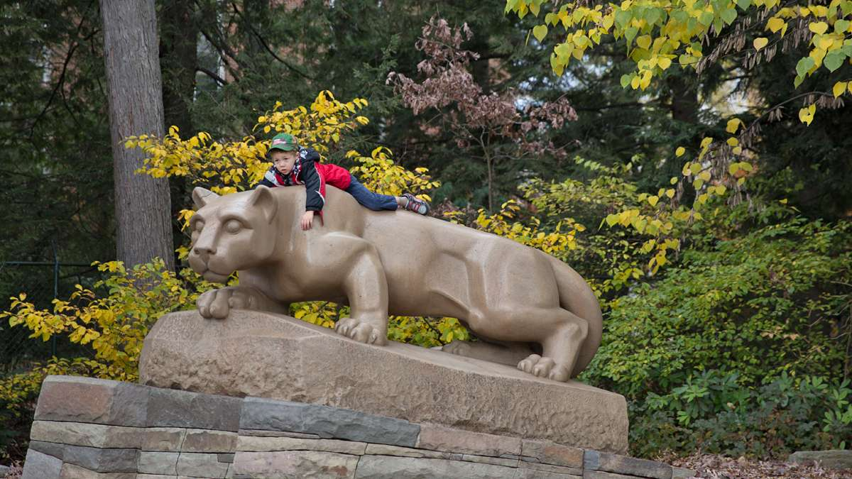 Brayden King, 4, lies on top of the Nittany Lion Shrine as his grandmother looks on. (Lindsay Lazarski/WHYY)