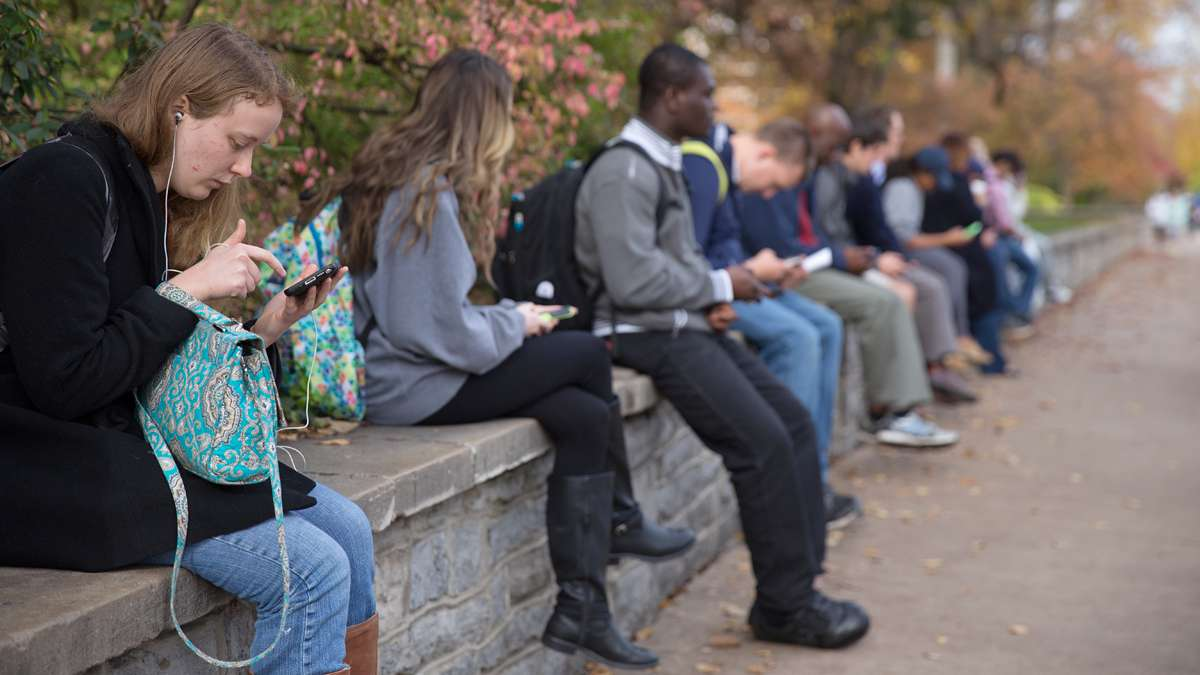 Emily Flanigan (far left), a Junior studying mechanical engineering at Penn State, waits at a bus stop with other students on College Avenue. (Lindsay Lazarski/WHYY)