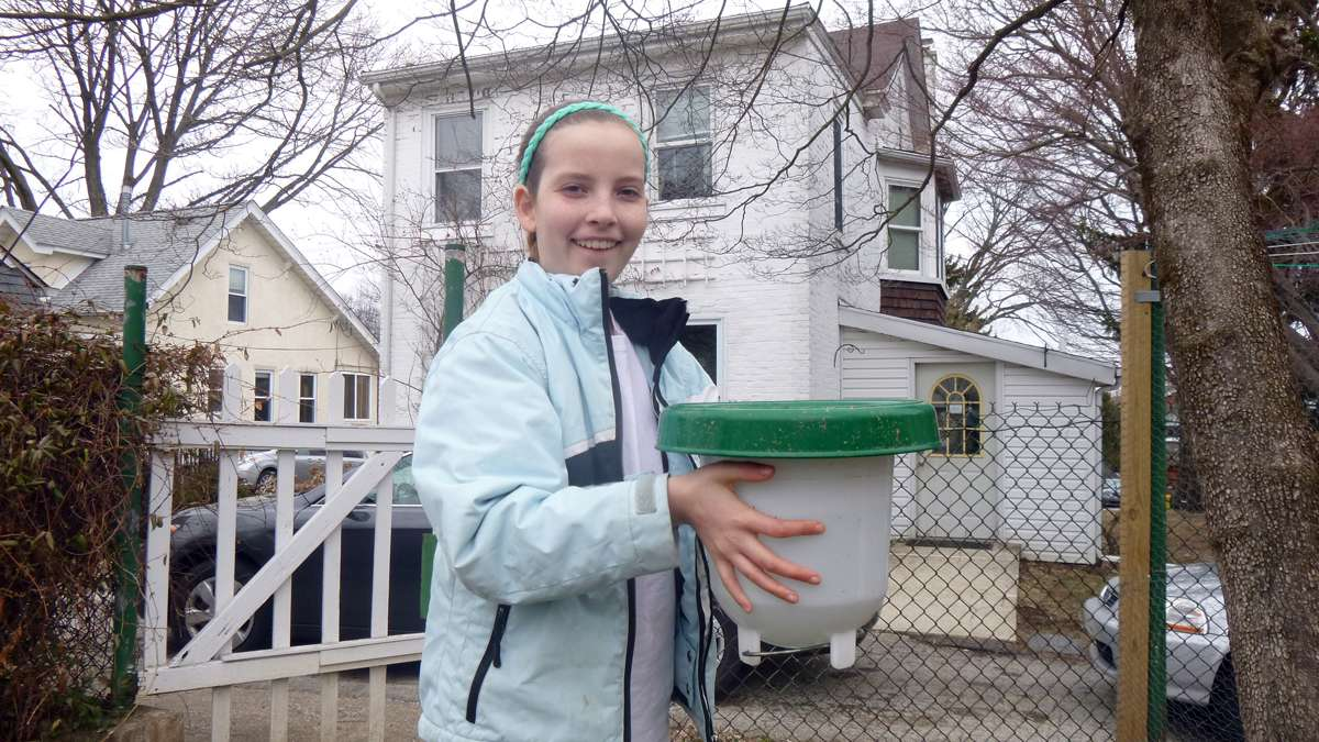 Ariadne Marg-Bracken, 13, with the chicken coop's watering trough. (Jennifer Lynn/WHYY)