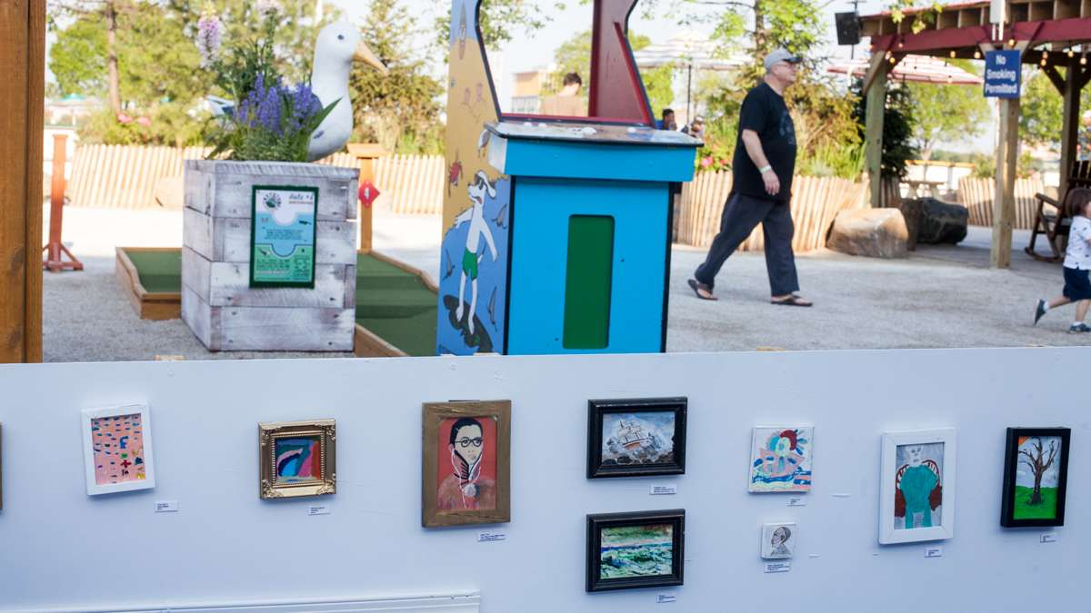 Framed art decorates the barrier to a portion of the mini golf course.