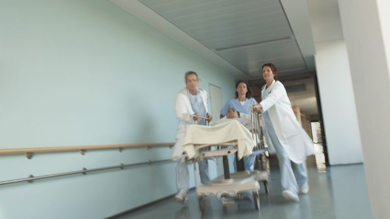 Hospital workers move a patient to surgery.  (<a href=