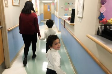 The Taweels arrived in the U.S. in January as Syrian refugees. Shortly after, they went to Einstein's pediatric clinic for their first comprehensive health exam in the U.S. Dr. Raghava Kavalla walks with the two boys, 6-year-old Ghassan and four-year-old Anas, to an exam room. (Elana Gordon/WHYY)