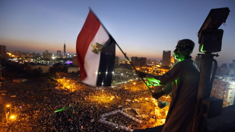 An Egyptian protester is shown waving a national flag over Tahrir Square, Cairo, in 2013, as opponents of President Mohammed Morsi gather. (AP Photo/Amr Nabil)