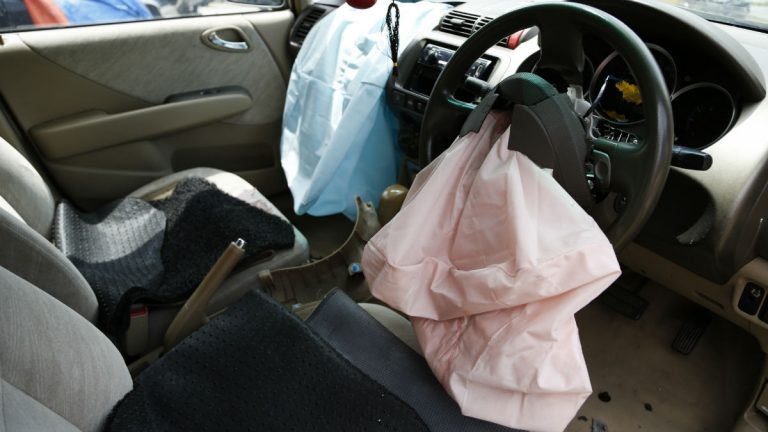 In this Monday, Nov. 7, 2016 photo, the exploded air bag that injured Rabiah binti Ibrahim, hangs from her steering wheel in her Honda City in Slim River, Malaysia. Five Malaysians have died in accidents linked to faulty Takata air bags that are at the center of one of the world's largest auto recalls. (AP Photo/Lim Huey Teng)
