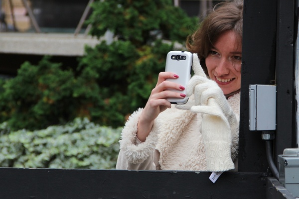 <p>Kate Pukhovich smiles as she photographs the tango dancers in Love Park. (Emma Lee/for NewsWorks)</p>