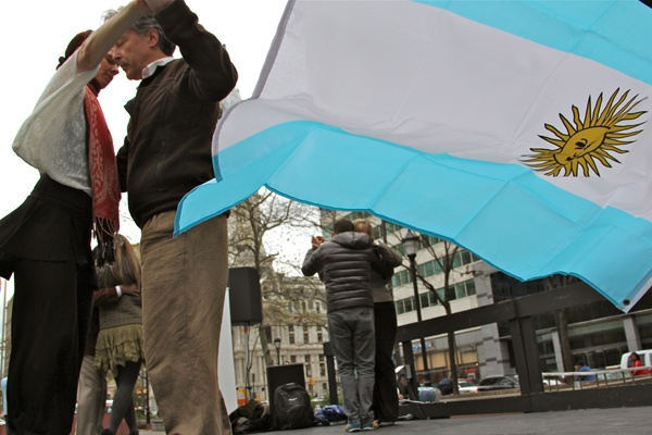 <p>The Argentine flag flaps in a chilly breeze as dancers demonstrate Argentine tango as part of a cultural outreach organized by the Embassy of Argentina. (Emma Lee/for NewsWorks)</p>