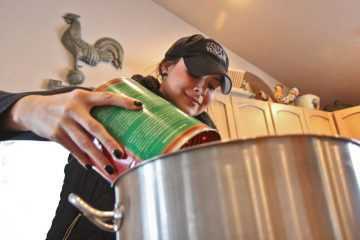 Katie Robbins add Contadina crushed tomatoes to the batch of Taste of Tuscany pasta sauce. (Kimberly Paynter/WHYY)