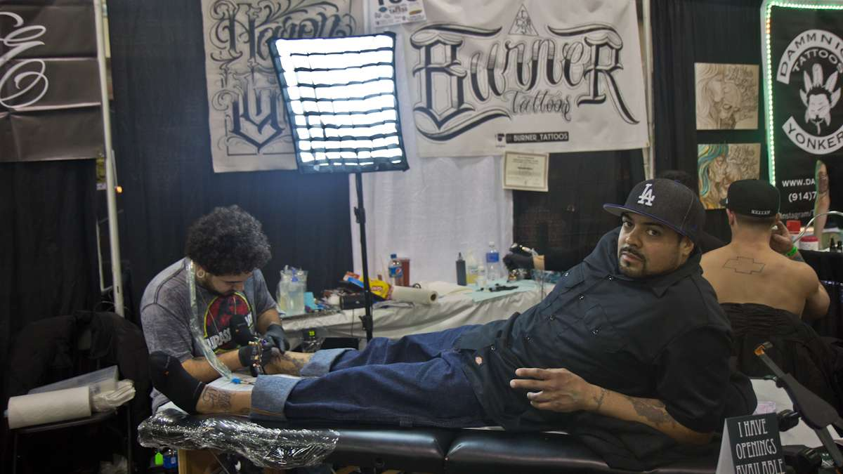 Daniel Santos receives two tattoos from Aaron Garcia, one that says Guatemala and one that says Puerto Rico, to honor his heritage. (Kimberly Paynter/WHYY)