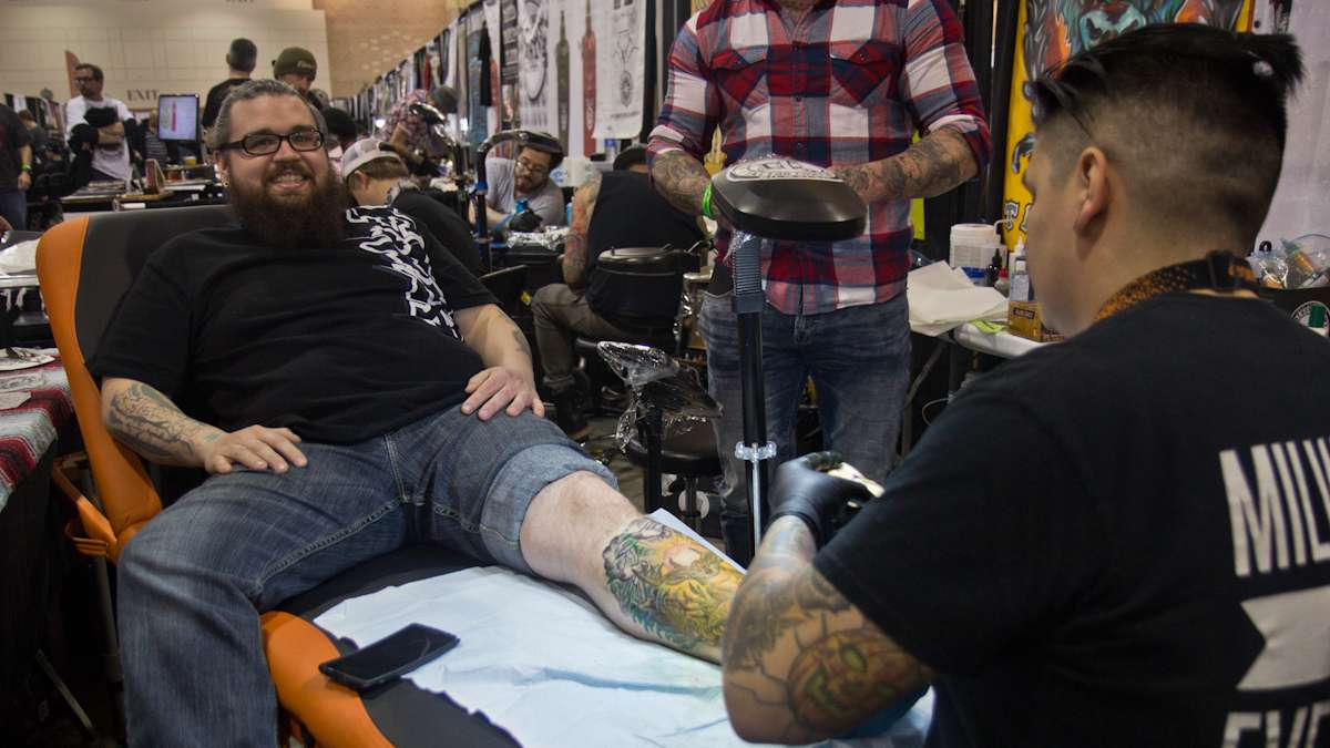 Artist Tom Aladna tattoos a deer on Chet Wescoat because of Wescoat's love of hunting. (Kimberly Paynter/WHYY)