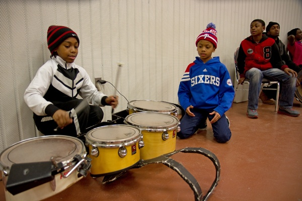 <p>Tawanda Jones' son Requan, 8, (left) helps keep the beat for the Camden Sophisticated Sisters.  (Lindsay Lazarski/WHYY)</p>