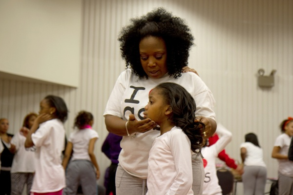 <p>Tawanda Jones, leader of Camden Sophisticated Sisters, with Da'Anah Harper, 6, reminds the team members to carry themselves with confidence.  (Lindsay Lazarski/WHYY)</p>