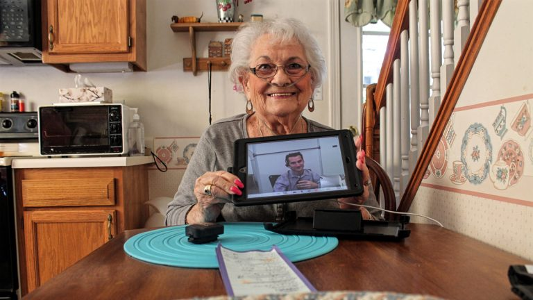 Naomi Coulter, 87, holds the iPad she uses to check in with her physician every morning. She credits Mercy's virtual home health program with helping her stay out of the hospital. (Ryan Delaney/for WHYY)