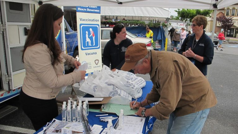 Residents in Point Pleasant Beach sign up to get free tetanus booster shot being offered by Ocean County Health Department at its mobile outreach van (Phil Gregory/for NewsWorks)