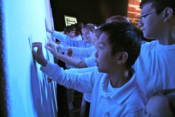 <p>Victor Ung and his 5th grade classmates from Meredith Elementary School touch a representation of the iceberg that sank the Titanic. The wall is refrigerated to conjure the frigid conditions at the time of the sinking. (Emma Lee/for NewsWorks)</p>