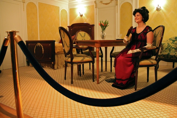 <p>Franklin Institute volunteer Karen Knodel portrays the Countess of Roth sitting in the recreation of a first class cabin. (Emma Lee/for NewsWorks)</p>