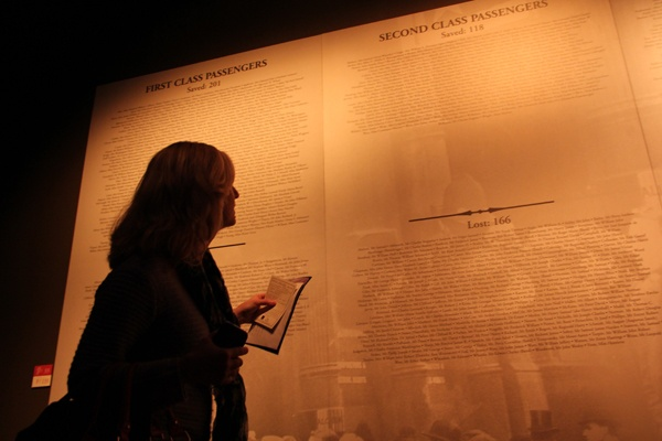 <p>Joanne Concepcion, chaperoning a group of 5th graders from Meredith Elementary School, tries to find the name on her boarding pass in the list of passengers and crew that concludes the exhibit. (Emma Lee/for NewsWorks)</p>