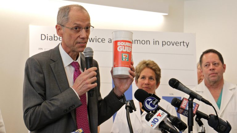 Philadelphia Health Commissioner Thomas Farley holds up a large soda container during a press conference at Puentes de Salud Health Clinic where doctors gathered to tout the health benefits of the sugary drinks tax. (Emma Lee/WHYY)