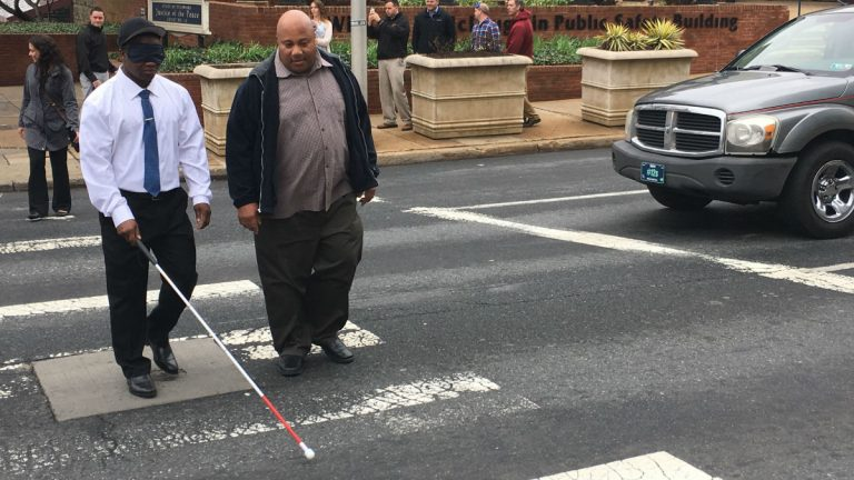 Wilmington Police officers walk across Walnut St. using blindfolds to experience what life is like for those who are visually impaired. (Mark Eichmann/WHYY)