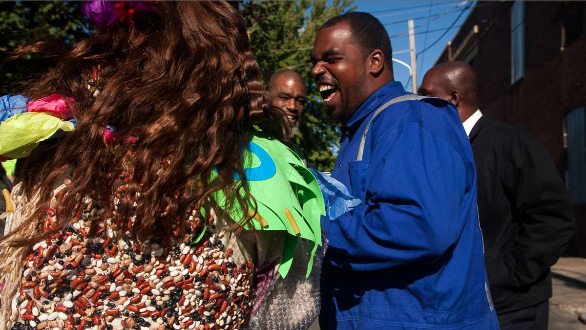 Jenny Drumgoole (aka Soxx) laughs with sanitation workers. Her specially made dress was covered in beans and pasta. (Brad Larrison/for NewsWorks)