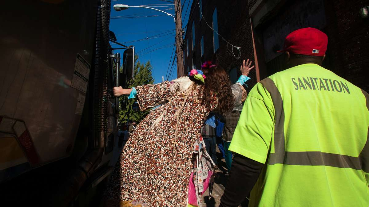 Soxx waves to sanitation workers from the back of a trash truck. (Brad Larrison/for NewsWorks)
