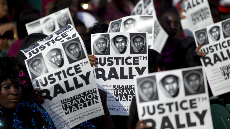 People at a rally in downtown Miami in 2012 hold signs demanding justice for Trayvon Martin. (AP Photo/J Pat Carter, file)