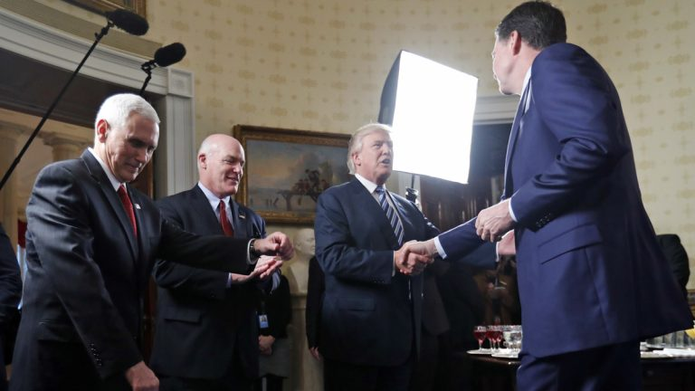 Vice President Mike Pence, left, and Secret Service Director Joseph Clancy stand as President Donald Trump shakes hands with FBI Director James Comey during a reception for inaugural law enforcement officers and first responders in the Blue Room of the White House, Sunday, Jan. 22, 2017 in Washington. (AP Photo/Alex Brandon, file)