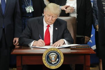 President Donald Trump signs an executive order for border security and immigration enforcement improvements
