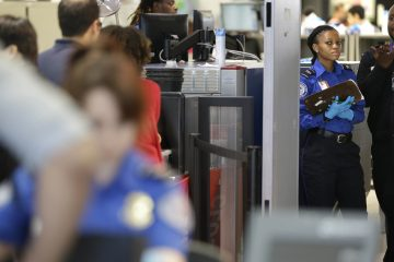 Transportation Security Administration employees are shown at work before Memorial Day weekend. (AP Photo/Seth Wenig)