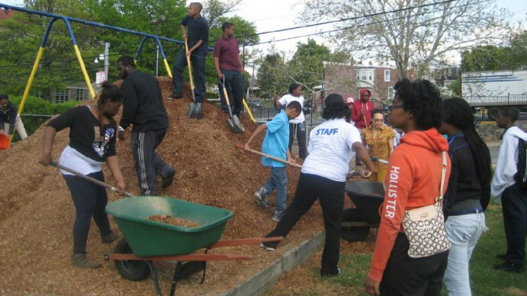 Workers add mulch underneath playground  equipment at Father Tucker Park in Wilmington's Little Italy section. (photo via WestSideGrows.org)